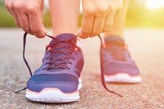 La muchacha implica cordones en zapatillas de deporte en el camino mientras que activa, pierna y las zapatillas de deporte, luz d Fotografía de archivo