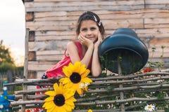 La muchacha inclinada en la cerca de mimbre Fotos de archivo