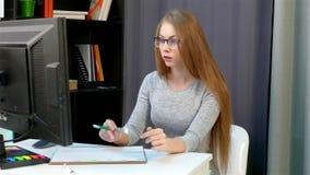 La muchacha incorpora datos en el registro del monitor de computadora metrajes