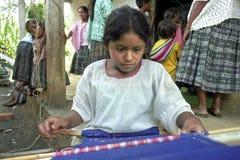 La muchacha india guatemalteca está trabajando en telar Imagen de archivo libre de regalías