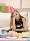 La muchacha infeliz en sombrero del partido se sienta con los regalos Fotografía de archivo