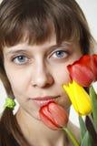La muchacha inhala el aroma de tulipanes Imágenes de archivo libres de regalías