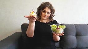 La muchacha integral hermosa está sentando en el sofá hambriento una torta de la ensalada, postre, dulce, opción almacen de metraje de vídeo