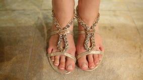 La muchacha intenta encendido el pie de las sandalias en zapatería Fotos de archivo libres de regalías