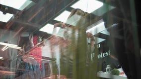 La muchacha intenta encendido una nueva camiseta elegante en la tienda Compras, visión a través de la ventana almacen de video