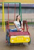 La muchacha intenta retrasar en un coche del juguete Fotografía de archivo
