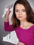 La muchacha interrumpe un papel con una rabia Imágenes de archivo libres de regalías