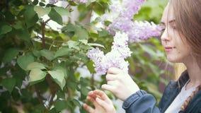 La muchacha, interrumpe una puntilla de la lila y de las aspiraciones, día de verano, a cámara lenta almacen de video