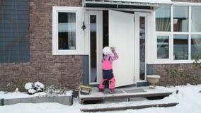 La muchacha, invierno del niño abre la puerta, entra en casa metrajes