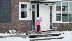 La muchacha, invierno del niño abre la puerta, entra en casa almacen de metraje de vídeo