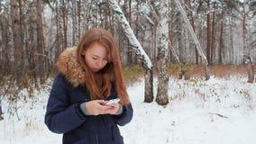 La muchacha iwalking en el bosque del invierno con el teléfono almacen de video