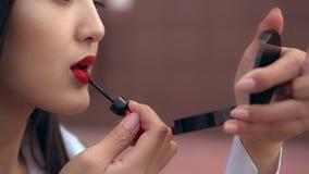 La muchacha japonesa hermosa pinta sus labios con la barra de labios roja Luce increíble de la persona almacen de video
