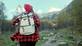 La muchacha joven activa del inconformista viaja a través del bosque, va a lo largo de la trayectoria entre las montañas Ella est almacen de metraje de vídeo