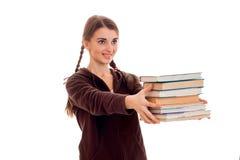 La muchacha joven alegre del estudiante con los libros en deporte marrón viste la sonrisa aislada en el fondo blanco años del est Imagen de archivo libre de regalías