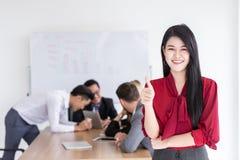 La muchacha joven asiática del negocio manosea con los dedos para arriba con la oficina imagenes de archivo