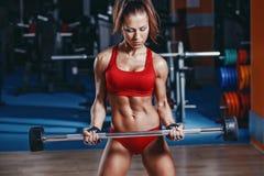 la muchacha joven atractiva del atletismo que hace el rizo del barbell del bíceps ejercita en gimnasio imágenes de archivo libres de regalías