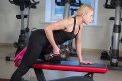 La muchacha joven atractiva del atletismo que hace pesas de gimnasia presiona ejercicios La aptitud muscled a la mujer en entrena Imagenes de archivo