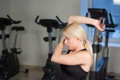 La muchacha joven atractiva del atletismo que hace pesas de gimnasia presiona ejercicios La aptitud muscled a la mujer en entrena Fotografía de archivo libre de regalías