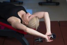 La muchacha joven atractiva del atletismo que hace pesas de gimnasia presiona ejercicios La aptitud muscled a la mujer en entrena Fotos de archivo libres de regalías