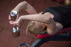 La muchacha joven atractiva del atletismo que hace pesas de gimnasia presiona ejercicios La aptitud muscled a la mujer en entrena Imágenes de archivo libres de regalías