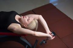 La muchacha joven atractiva del atletismo que hace pesas de gimnasia presiona ejercicios La aptitud muscled a la mujer en entrena Foto de archivo