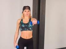 La muchacha joven atractiva del atletismo que hace pesas de gimnasia presiona ejercicios La aptitud muscled a la mujer en entrena Foto de archivo libre de regalías