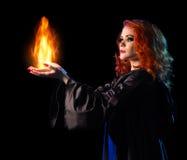 La muchacha joven de la bruja lleva a cabo el fuego aislado Imágenes de archivo libres de regalías