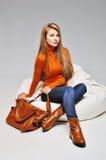 La muchacha joven de la moda que se sienta en ropa de moda en las botas de cuero con el bolso Imagen de archivo libre de regalías