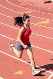 La muchacha joven de Latina que se ejecuta en pista pone en cortocircuito la tapa roja Foto de archivo