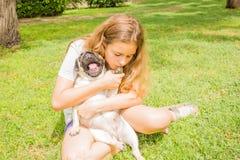La muchacha joven del adolescente abraza su perro del barro amasado en el parque en la hierba verde imagenes de archivo