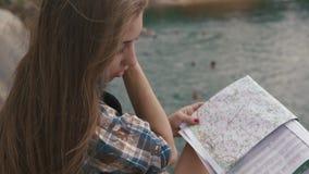 La muchacha joven del adolescente descansa sobre roca de la montaña encendido a orillas del lago del lago de la montaña y de la m metrajes