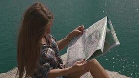 La muchacha joven del adolescente descansa sobre roca de la montaña sobre la superficie grande del agua del lago y de la mirada d almacen de metraje de vídeo