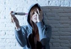 La muchacha joven del adolescente o la mujer joven en choque asustó después de prueba de embarazo positiva Imágenes de archivo libres de regalías