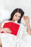 La muchacha joven del adolescente se cayó dormido en la cama después de leer un libro Fotos de archivo