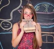 La muchacha joven del estudiante con el paquete de libros presenta cerca de la pizarra Imágenes de archivo libres de regalías