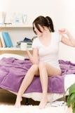 La muchacha joven del estudiante despierta en cama Foto de archivo