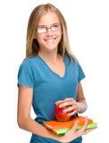 La muchacha joven del estudiante está sosteniendo el libro y la manzana Foto de archivo libre de regalías
