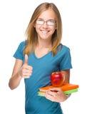 La muchacha joven del estudiante está sosteniendo el libro y la manzana Fotos de archivo libres de regalías