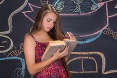 La muchacha joven del estudiante lee el libro delante de la pizarra de la escuela Imágenes de archivo libres de regalías
