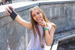 La muchacha joven del estudiante que hace el selfie y se relaja en parque de la ciudad Foto de archivo libre de regalías