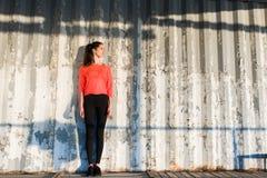 La muchacha joven del inconformista con una figura perfecta que presenta contra la calle empareda al aire libre Fotos de archivo