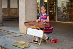 La muchacha joven del músico de la calle se sienta en la calle y los juegos para el viaje Foto de archivo