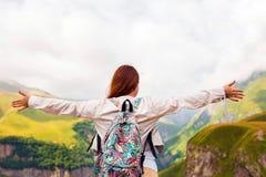 La muchacha joven del pelirrojo aumentó sus brazos hasta el sol en un fondo de montañas fotos de archivo libres de regalías