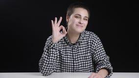 La muchacha joven del pelo corto muestra la muestra aceptable, sonriendo, riendo, fondo negro almacen de metraje de vídeo