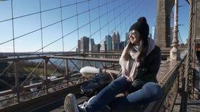 La muchacha joven e imprudente se sienta en el borde del puente de Brooklyn Nueva York almacen de metraje de vídeo