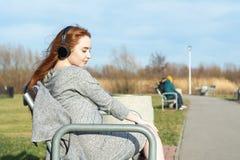 La muchacha joven, feliz del pelirrojo en la primavera en el parque cerca del río escucha la música a través de los auriculares i foto de archivo libre de regalías