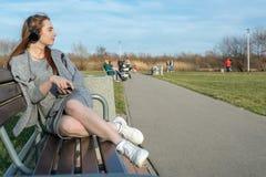 La muchacha joven, feliz del pelirrojo en la primavera en el parque cerca del río escucha la música a través de los auriculares i fotografía de archivo