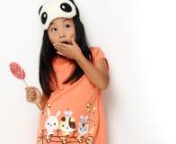 La muchacha joven feliz del pequeño niño con el lollypop dulce sorprendió la mirada de la esquina Imágenes de archivo libres de regalías