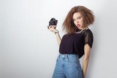 La muchacha joven hermosa del inconformista que sostiene la cámara hace las imágenes, fotos en la cámara, en vaqueros y una camis Imagenes de archivo