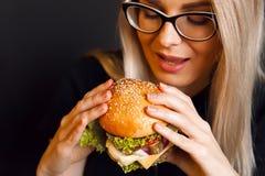 La muchacha joven, sana hermosa sostiene una hamburguesa grande sabrosa con la chuleta de la carne de vaca Imágenes de archivo libres de regalías